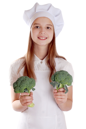 The girl in a suit of the cook with broccoli on isolated background Banco de Imagens