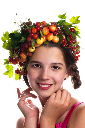 Smiling girl with a wreath of fruit on her head. Isolated Background 写真素材