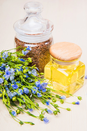 Linseed oil, flax seeds, and flowers on a light background.