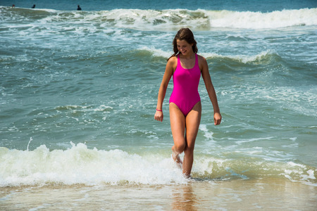 Sport girl-teenager in a pink bathing suit on background of ocean. Atlantic ocean. Porto, Portugal