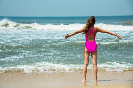 Sport Mädchen-Teenager in einem rosa Badeanzug auf Hintergrund des Ozeans. Atlantischer Ozean. Porto, Portugal