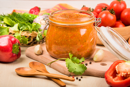 Tomato sauce (ketchup, adzhika) and vegetables on a beige table. Home preservation. Stock Photo