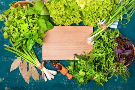 Verschillende kruiden (salade, dille, peterselie, koriander) op een houten achtergrond. Plaats voor tekst.