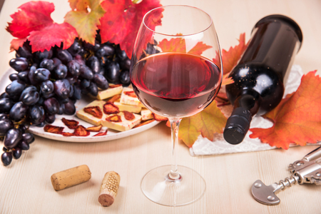 Still life with a bottle and a glass of red wine, grapes and chocolate with strawberries