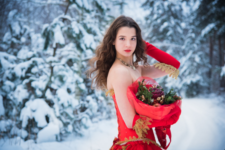 A girl in a fairy-tale image of a queen poses in a snow-covered winter forest. Long red dress, bouquet of fruits, red apples. Stock Photo