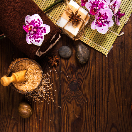 Spa concept with chocolate and candles on a wooden background.