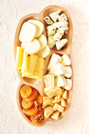 Set on a beige background. Different types of cheeses: Camembert, Parmesan, blue cheese, olives, honey, grapes.