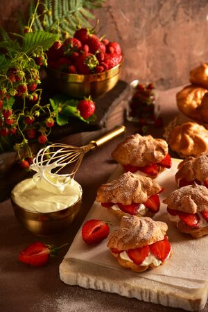 Eclairs custard cakes (shu, profiteroles) with strawberries on a dark background. Still life.