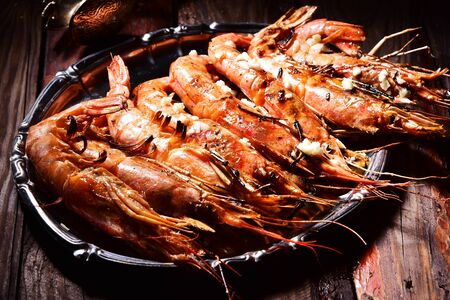 Beer and langoustines on a dark background.
