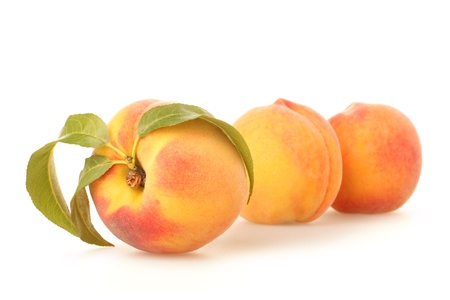 Ripe peach fruits with green leaves on white background