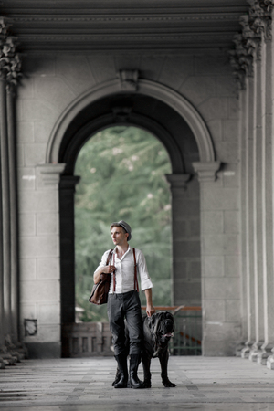 Man walking with grey dog in the city