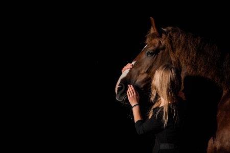 girl hugging a horse on a dark background Stockfoto