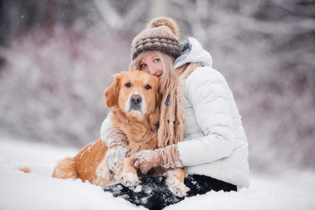 retriever sitting with a girl in the snow