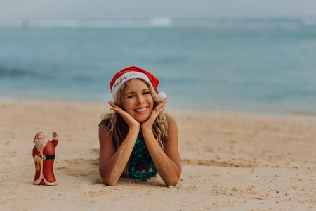 Portrait of happy girl on tropical beach in santa red hat sit and smiling, hold pineapple in sand with ocean and little Santa toy Stock Photo