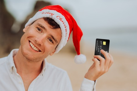 happy smiling and laughing handsome boy men in red hat Santa claus and white shirt stay on beach and hold credit card in ocean