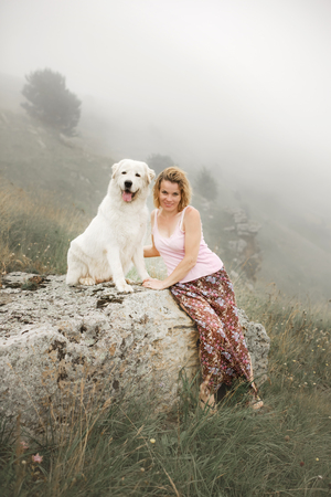 beautiful women and two white dogs morema sit on rock in fog Stock Photo