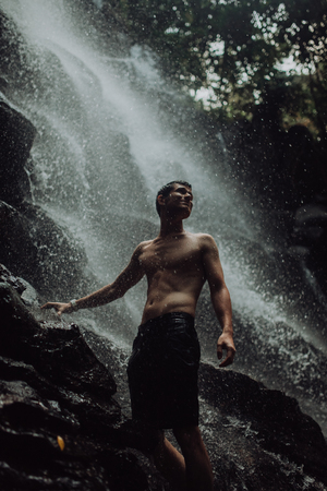 lean muscular Man look at waterfall in dark and smiling