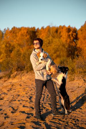 Porträt eines glücklichen Mannes mit zwei lustigen Border-Collie-Hunden am Strand am Meer. Herbstgelber Wald im Hintergrund Standard-Bild