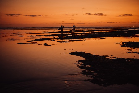 two Silhouette of surfers .sand and beach with sunset dark red light 免版税图像