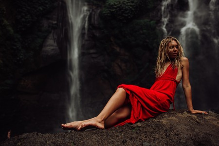 sexy young Girl in red dress at amazing Waterfall Bali