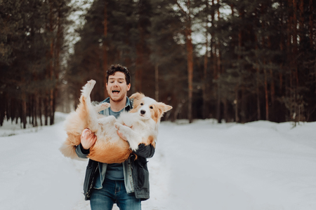 cheerful cute laughing and smiling guy in jeans clothes with dog border collie red on his hands in snowy forest. concept of winter . winter vacation. space for text 免版税图像