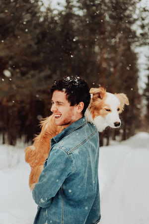 cheerful cute laughing and smiling guy in jeans clothes with dog border collie red on his hands in snowy forest. concept of winter . winter vacation