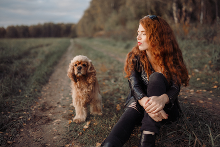 cool rokenrola girl in black clothes sits on the edge of the forest and plays with her dog Spaniel Stok Fotoğraf