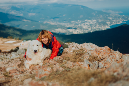 Happy cheerful white dog, shepherd dog of the Abruzzi Maremma with a woman in red lay on field n the mountains. sea and city view