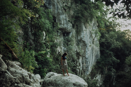 Young and woman sit on the beautiful waterfall in the jungle beside cliff