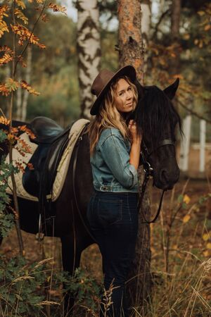 hipster girl with a horse in the woods smiling