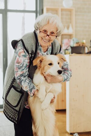 An elderly woman with dog in the kichen