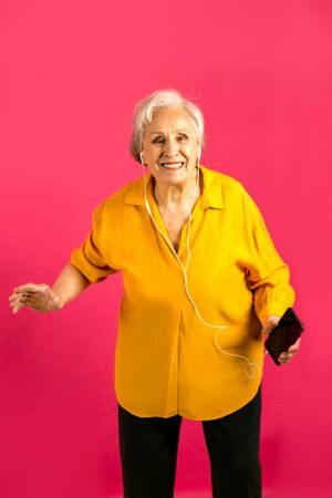 aged woman making selfie with peace sing and smilling. Portrait of handsome expressive grandmother in light blue suit Studio shot, isolated on gray background