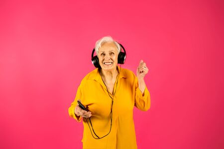 aged woman making selfie with peace sing and smilling. Portrait of handsome expressive grandmother in light blue suit Studio shot, isolated on gray background listen to music