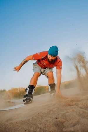 Tourist Sandboarding In the Desert Man jumps in and does the trick, outdoor Stok Fotoğraf - 131327007