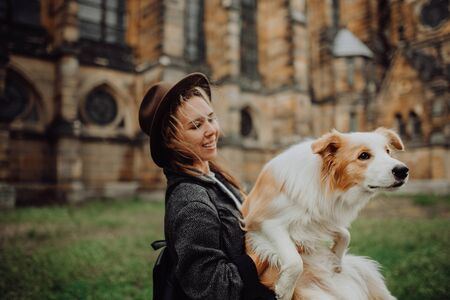 Beautiful woman, dressed elegantly, embracing her red border collie dog. Church in Gothic style on the background