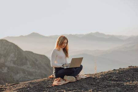 inspirational image of stylish millennial hipster female works with laptop, sunset light and mountain view. freelance woman works outside