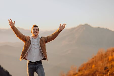 carefree outstretched arms, man looking at the camera and smiling