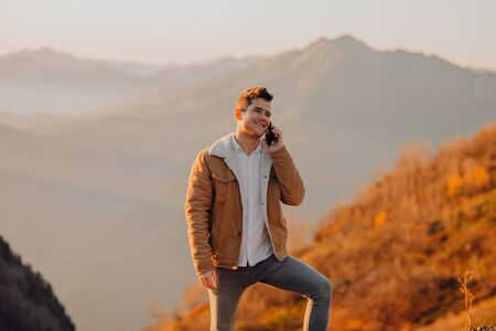 man with phone looking at the camera and smiling in the mountains Imagens