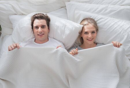 Couple young in love smiling lying cover under white blanket in bed