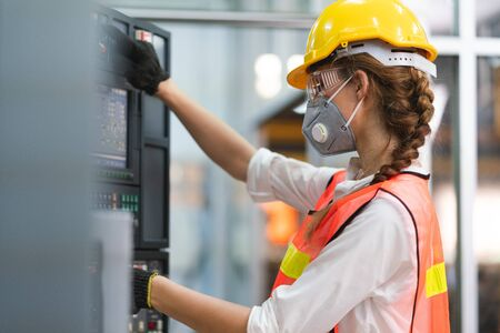 Female engineer wear face mask with safety vest and yellow helmet operating control CNC Machinery at factory