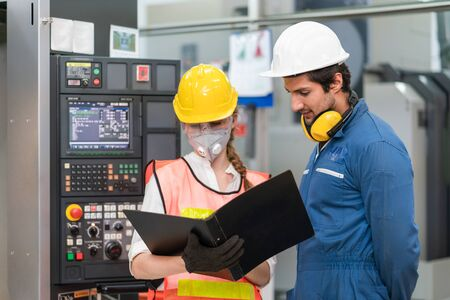 Female engineer wearing face mask with safety vest and protective helmet with male engineer looking document operating control CNC Machinery at factory