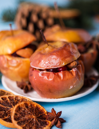 Baked apples with cinnamon on rustic background. Autumn or winter dessert. Closeup photo of a tasty baked apples with christmas decoration