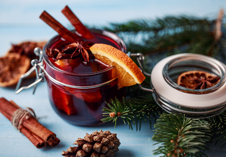 Mulled wine in a glass. Christmas hot mulled wine in a glass with spices and citrus fruit. Mulled wine with cinnamon anise and orange. Christmas atmosphere