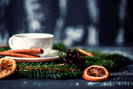 A cup of coffee with cinnamon on a dark wooden background. A cup of coffee in christmas decorations