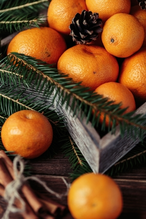 Tangerines with christmas decoration on rustic wooden background. Tangerines with spruce. Christmas decoration Archivio Fotografico