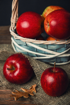 Herbstzusammensetzung mit frischen roten Äpfeln in einem hölzernen Korb auf rustikalem hölzernem Hintergrund . Rote Äpfel auf Leinen Hintergrund Standard-Bild - 92276353