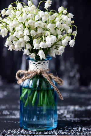 Lily of the valley on a dark wooden background. Lily of the valley bouquet. Space for text. 免版税图像 - 92422391