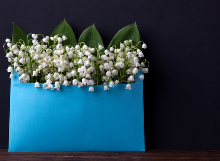 Lily of the valley on a dark wooden background. Lily of the valley bouquet. Space for text.