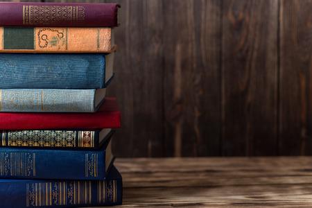Wiele starych książek na drewnianym tle. Źródło informacji. Otwarta książka wewnątrz. Biblioteka domowa. Wiedza to potęga