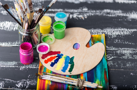 Art and craft tools.Artists brush, canvas. Wooden art palette with tubes of acrylic paints.Artists workshop.Art picture with copy space and for add text.Artist workplace background.Paints brushes